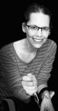 Hemophilia News Today \ In a black-and-white photo, columnist Shellye Horowitz smiles while infusing factor product.